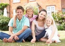 De Zitting van de familie in Tuin samen royalty-vrije stock afbeeldingen