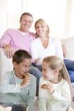De zitting van de familie in woonkamer die koekjes eet stock foto's