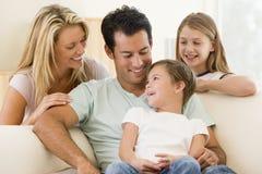 De zitting van de familie in woonkamer het glimlachen Royalty-vrije Stock Foto's