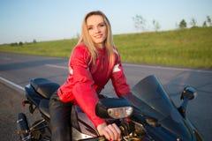 De zitting van de fietservrouw op een motorfiets stock afbeeldingen