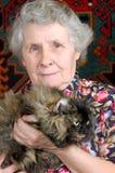 De zitting van de grootmoeder met kat op haar handen Stock Afbeeldingen