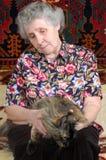 De zitting van de grootmoeder met kat op haar handen Royalty-vrije Stock Foto's