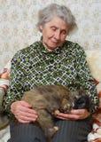 De zitting van de grootmoeder met kat op haar handen royalty-vrije stock afbeeldingen