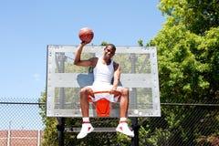 De zitting van de het basketbalspeler van de kampioen in hoepel stock fotografie