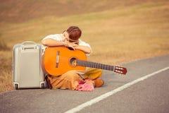 De zitting van de hippievrouw op een plattelandsweg stock afbeelding