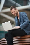 De Zitting van de jonge Mens in Bank met zijn Laptop Stock Afbeeldingen