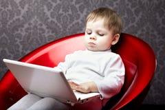 De zitting van de jongen als voorzitter met laptop stock fotografie