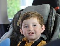 De zitting van de jongen in de zetel van de kindauto Royalty-vrije Stock Foto's