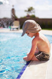 De zitting van de jongen in een pool royalty-vrije stock afbeeldingen