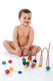 De zitting van de jongen en het lachen dichtbij zijn speelgoed Stock Afbeeldingen
