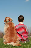 De Zitting van de jongen en van de Hond op een Heuvel Stock Afbeelding