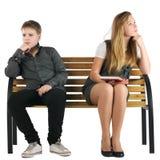 De zitting van de jongen en van het meisje op een bank Stock Foto