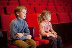 De zitting van de jongen en van het meisje op leunstoelen bij bioskoop royalty-vrije stock fotografie