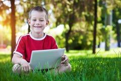 De zitting van de jongen met laptop op het gras Stock Foto's