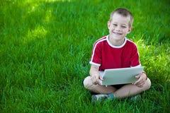 De zitting van de jongen met laptop op het gras Royalty-vrije Stock Fotografie