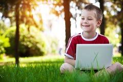 De zitting van de jongen met laptop op het gras Stock Afbeeldingen