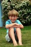De zitting van de jongen neer in gras Stock Afbeelding