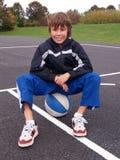 De zitting van de jongen op basketbal Royalty-vrije Stock Foto's