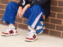 De zitting van de jongen op basketbal Royalty-vrije Stock Foto