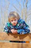 De zitting van de jongen op een bank Royalty-vrije Stock Foto