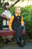 De zitting van de jongen op een bank en een meisje in mooie kleding Royalty-vrije Stock Afbeeldingen