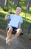 De zitting van de jongen op een schommeling Stock Foto