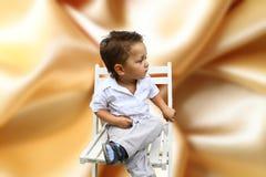 De zitting van de jongen op een stoel Stock Foto