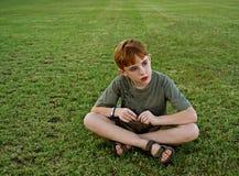 De zitting van de jongen op gras royalty-vrije stock afbeelding