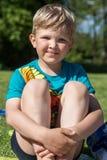 De zitting van de jongen op het gras Royalty-vrije Stock Afbeelding