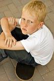 De zitting van de jongen op skateboard Stock Afbeeldingen