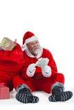 De zitting van de Kerstman naast gift die een muntnota tellen Stock Afbeeldingen