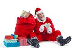 De zitting van de Kerstman naast gift die een muntnota tellen Stock Fotografie