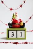De zitting van de Kerstman op kubussen die datum dertig eerst op witte achtergrond met rode slinger tonen Stock Foto