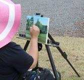 De zitting van de kunstenaarsdame en buiten het schilderen op canvas. royalty-vrije stock fotografie