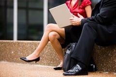 De zitting van de man en van de vrouw met laptop Stock Afbeelding