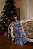 De zitting van de maniervrouw op bank voor Kerstboom stock foto's