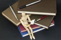 De zitting van de Maniquilezing op een berg van boeken en pennen stock afbeeldingen