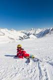De zitting van de meisjesskiër op een skihelling Stock Afbeeldingen