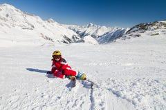 De zitting van de meisjesskiër op een skihelling Stock Foto