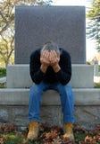 De zitting van de mens bij gravesite Royalty-vrije Stock Afbeelding