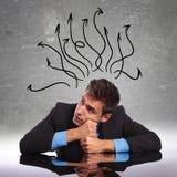 De zitting van de mens bij zijn bureau met zijn mening in alle richtingen Royalty-vrije Stock Foto