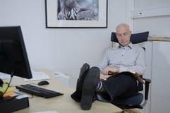 De zitting van de mens in bureau en lezing de krant Royalty-vrije Stock Afbeeldingen