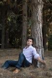De zitting van de mens dichtbij een boom Royalty-vrije Stock Afbeeldingen
