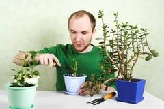 De zitting van de mens dichtbij lijst met het tuinieren apparatuur Stock Foto's