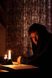 De zitting van de mens door kaarslicht Royalty-vrije Stock Foto's