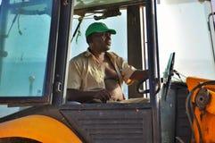 De zitting van de mens in een tractor Royalty-vrije Stock Afbeeldingen