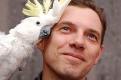 De zitting van de mens en van de papegaai op de schouder royalty-vrije stock foto's