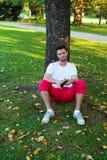 De zitting van de mens onder een boom Royalty-vrije Stock Afbeeldingen