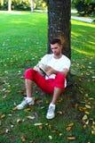 De zitting van de mens onder een boom die een boek leest Stock Afbeeldingen