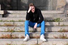 De zitting van de mens onderaan buitenkant kijkt ongerust gemaakt Stock Foto